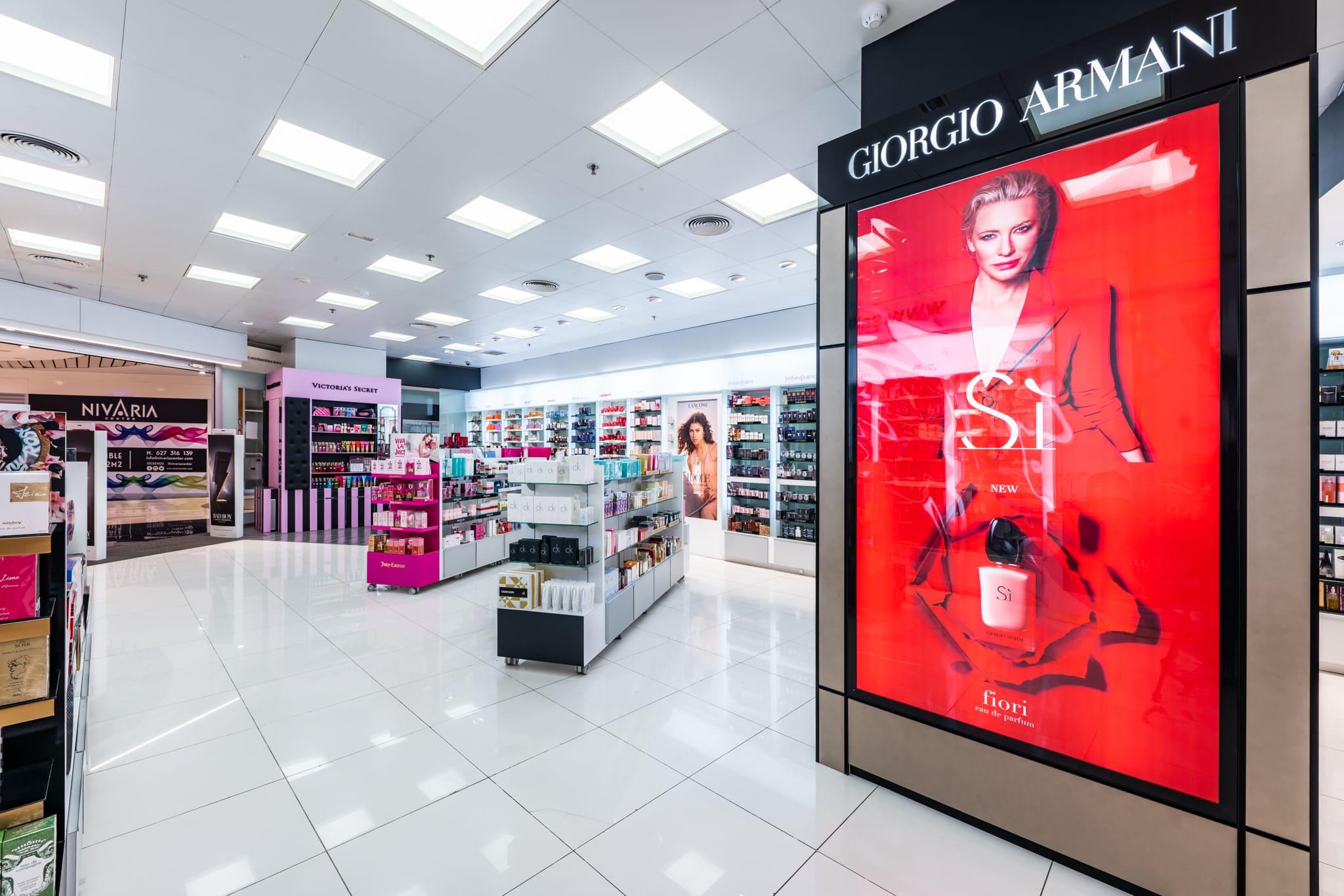 Imagen perfumería columna Armaní sí y fondo góndolas y perfumería